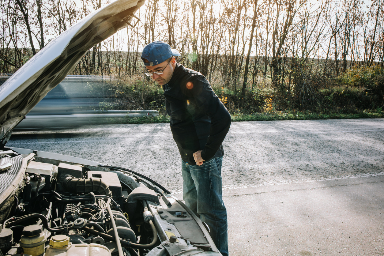 Man inspecting underneath car bonnet